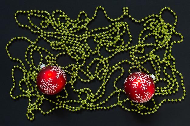 휴일 배경, 눈송이와 검정색 배경에 녹색 밝은 장식 구슬이 있는 빨간색 크리스마스 공, 평평한 평지, 위쪽 전망