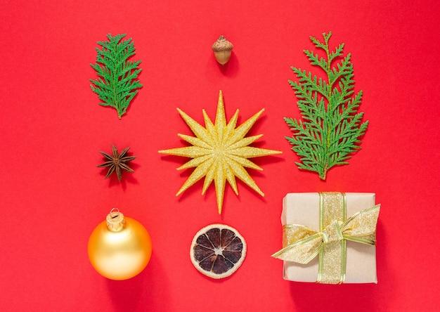 휴일 배경, 크리스마스 장식 세트, 선물 상자, 크리스마스 공이 있는 금별, thuja 나뭇가지, 도토리, 마른 감귤류가 있는 스타 아니스, 평평한 평지, 위쪽 전망