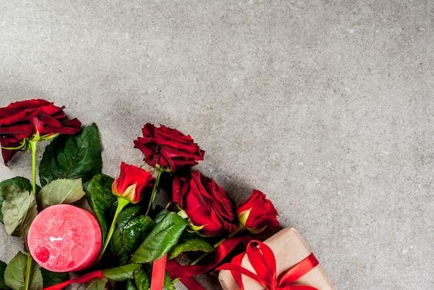 休日の背景、バレンタインの日。赤いバラの花束、赤いリボン、ラップされたギフトボックスと赤いキャンドルで結ぶ。灰色の石のテーブルにコピースペース平面図