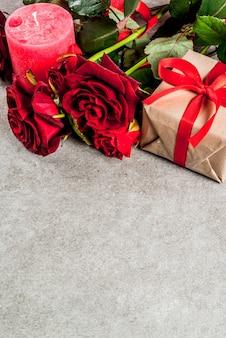 休日の背景、バレンタインの日。赤いバラの花束、赤いリボン、ラップされたギフトボックスと赤いキャンドルで結ぶ。灰色の石のテーブルにコピースペース