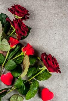 休日の背景、バレンタインの日。赤いバラの花束、ラップされたギフトボックス付きの赤いリボンで結ぶ。灰色の石のテーブルにコピースペース平面図