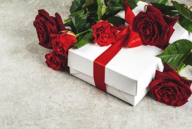 休日の背景、バレンタインの日。赤いバラの花束、ラップされたギフトボックス付きの赤いリボンで結ぶ。灰色の石のテーブルにコピースペース