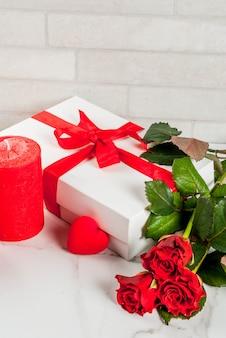 休日の背景、バレンタインの日。赤いバラの花束、ラップされたギフトボックス付きの赤いリボンで結ぶ。白い大理石のテーブルにコピースペース