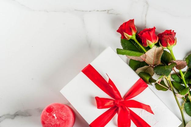 休日の背景、バレンタインの日。赤いバラの花束、赤いリボンとネクタイ、ラップされたギフトボックス。白い大理石のテーブルトップビュー