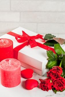 休日の背景、バレンタインの日。赤いバラの花束、赤いリボンとネクタイ、ラップされたギフトボックス。白い大理石のテーブルの上