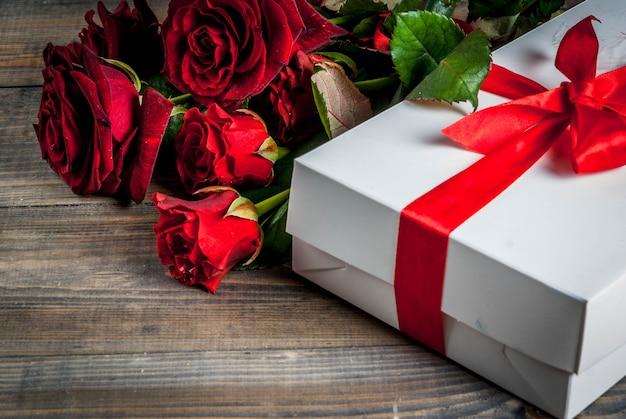 休日の背景、バレンタインの日。赤いバラの花束、ラップされたギフトボックス付きの赤いリボンで結ぶ。木製のテーブルにコピースペース