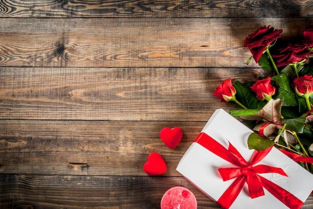 休日の背景、バレンタインの日。赤いバラの花束、赤いリボンとネクタイ、ラップされたギフトボックス。木製のテーブルトップビュー
