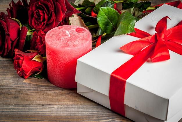 休日の背景、バレンタインの日。赤いバラの花束、赤いリボンとネクタイ、ラップされたギフトボックス。木製のテーブルの上