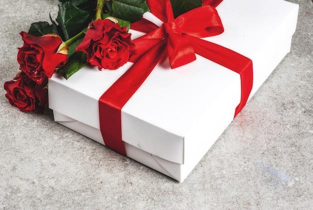 休日の背景、バレンタインの日。赤いバラの花束、赤いリボン、ネクタイギフトボックス