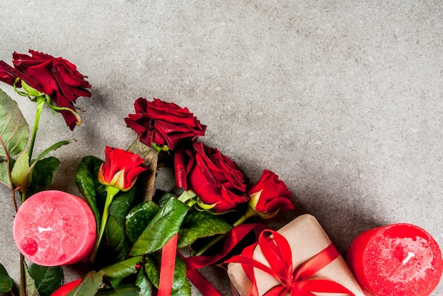 Holiday  background, valentine's day. bouquet of red roses, tie with a red ribbon, with wrapped gift box and red candle top view