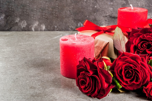 Holiday  background, valentine's day. bouquet of red roses, tie with a red ribbon, with wrapped gift box and red candle