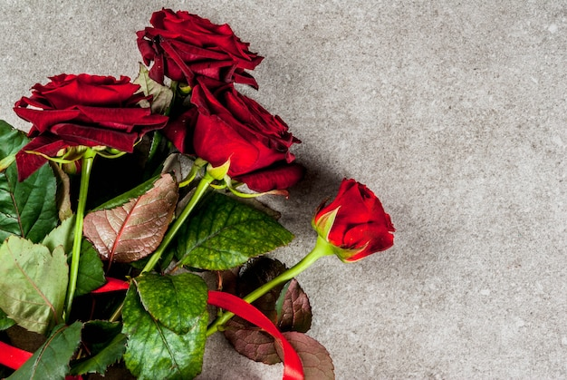 Holiday  background, valentine's day. bouquet of red roses, tie with a red ribbon, with wrapped gift box and red candle.