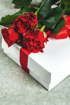 Holiday  background, valentine's day. bouquet of red roses, tie with a red ribbon, with wrapped gift box