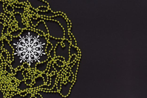 휴일 배경, 흰색 눈송이 및 검정색 배경에 녹색 밝은 장식 구슬, 평평한 평지, 위쪽 보기