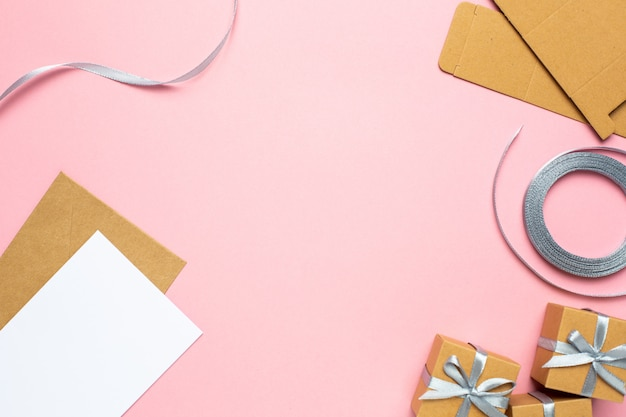 Holiday background with gift in boxs composition and ribbon on pink paper