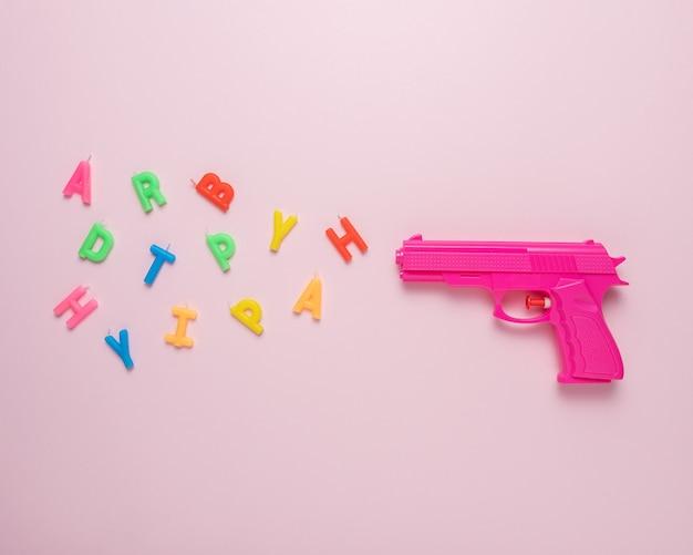 ピンクの銃と誕生日のキャンドルと休日の背景
