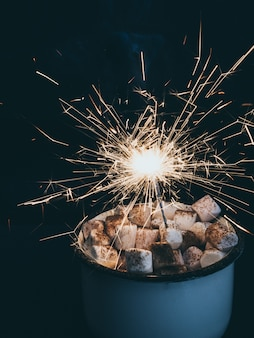 Holiday background with sparkler, cup with marshmallow. copy space.