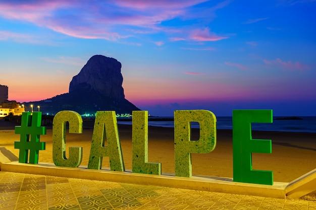 カルペアリカンテの街の岩の隣の夜のホリデービーチ。
