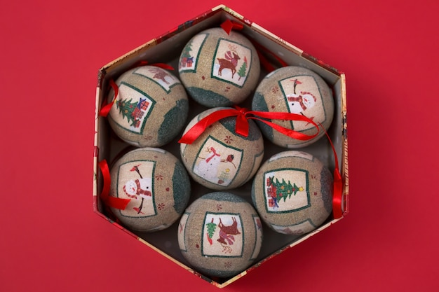 In the holiday box are several vintage christmas tree balls on a red paper background.