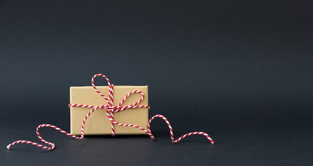 Holiday box with red ribbon on black
