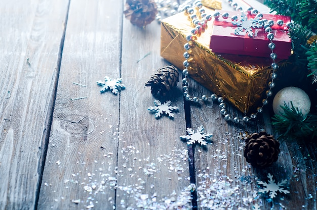 Holiday boxes with beads on wooden background.