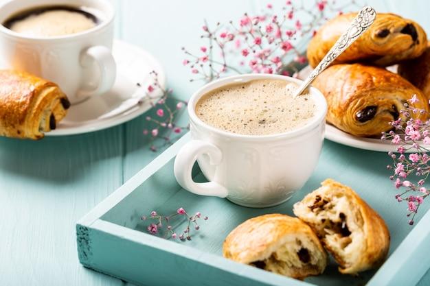 ターコイズブルーの表面に一杯のコーヒー、ミニ焼きたてのクロワッサンチョコレートパン、カーネーションの花で休日の休憩