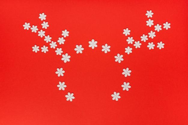 休日の明るい背景、赤い背景の上の白い雪のクリスマス鹿マスク