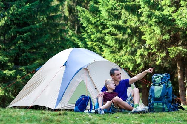 休日のキャンプ。父親は、森でハイキングした後、テントの近くで休憩を取って、息子に何かを見せます。幸せな家族関係と健康的なライフスタイル。