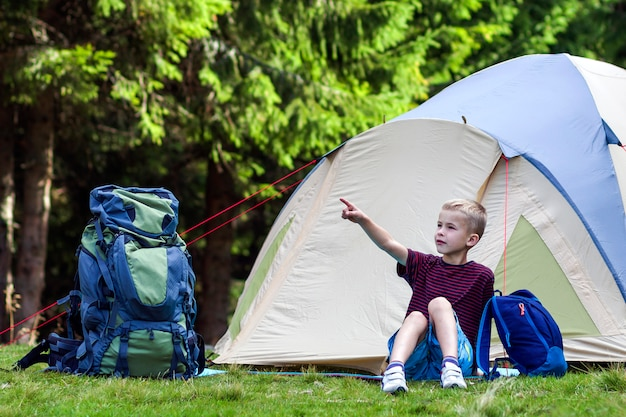 Holiday camping. young boy sitting in front of a tent near backpacks taking rest after hiking in the forest shows something in the trees. traveling and outdoors activities.
