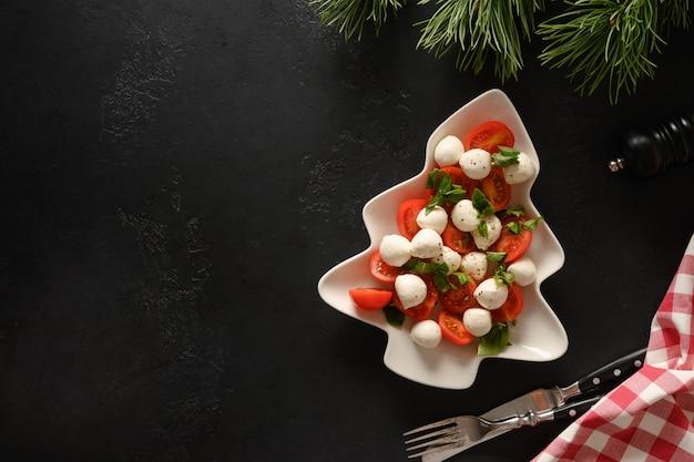 お祝いのクリスマスパーティーのためのクリスマスツリーのプレート形のホリデーカプレーゼサラダ