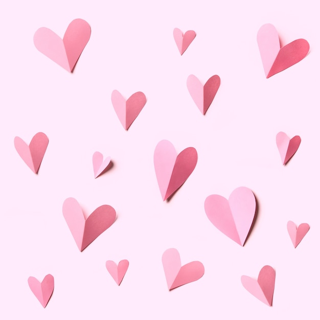 홀리데이 카드. 흰색 배경에 고립 된 분홍색 종이로 만든 심장. 엽서 장식용 질감입니다.