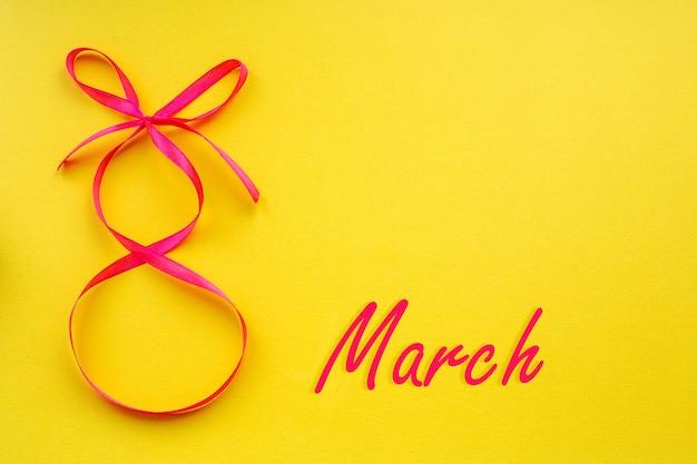 국제 여성의 날 노란색 배경에 8자 모양의 분홍색 리본이 달린 크리스마스 카드