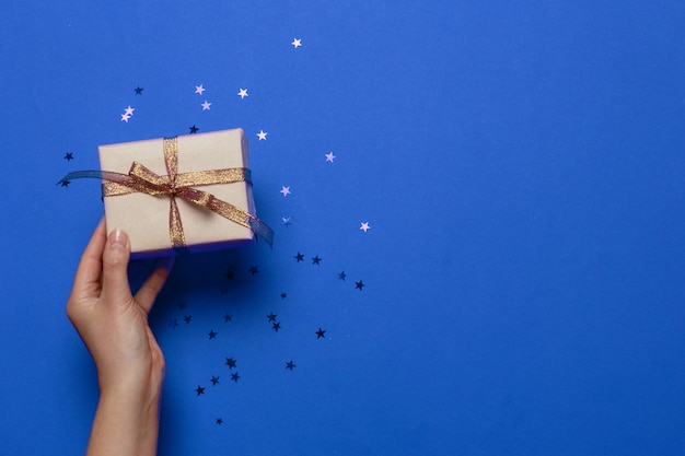 Holiday card of woman hand hold gift box on a blue