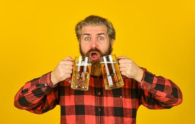 Праздник. день отца. концепция вечеринки по случаю дня рождения. алкогольный. жаждущий мужчина пьет пиво в баре паба. пиво с пеной. битник пьет пиво. зрелый бородатый парень держит пивной бокал. привет, тост.