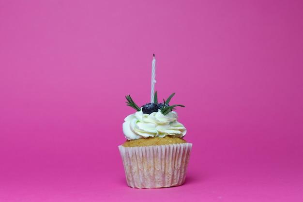 Праздник, праздник, приветствие и концепция вечеринки - кекс на день рождения с одной зажженной свечой на розовом фоне