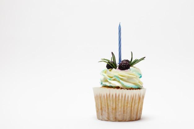 Праздник, праздник, приветствие и концепция вечеринки - кекс на день рождения с одной зажженной свечой на белой поверхности