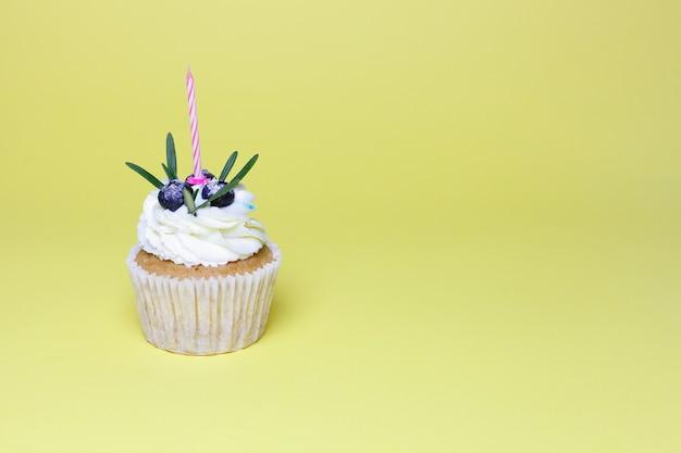Праздник, праздник, приветствие и концепция вечеринки - кекс на день рождения с одной зажженной свечой на желтом фоне