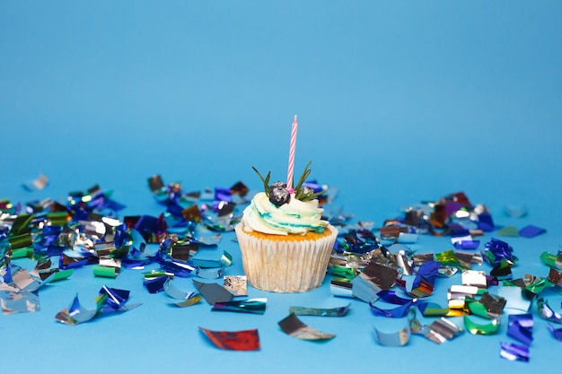 Holiday, celebration, greeting and party concept - birthday cupcake with one burning candles over blue surface, confetti