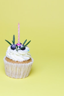 Holiday, celebration, greeting and party concept - birthday cupcake with one burning candles over yellow background