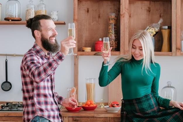 휴일 축하. 재미, 현대 부엌에서 샴페인을 마시는 행복 한 커플.