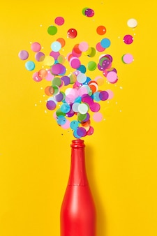 Holiday champagne red painted bottle with multicolored glitter as a bubbles foam on an yellow background, copy space. flat lay.