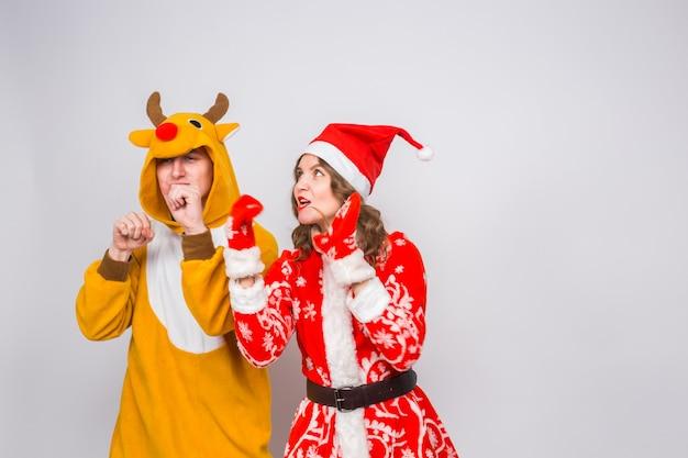 休日、クリスマス、楽しいコンセプト-鹿の衣装とサンタクロースの服を着た面白いカップルが白い壁で踊っています。