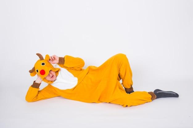 休日、クリスマス、人々の概念-白い床に横たわるサンタクロースの鹿の衣装の男