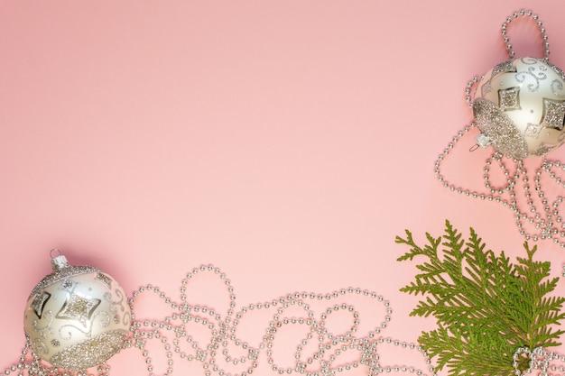 Праздничный новогодний фон, еловые ветки и серебряные декоративные бусины, новогодние шары на розовом фоне, плоская планировка, вид сверху