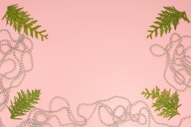 휴일 크리스마스 배경, 전나무 가지 및 분홍색 배경에 은색 장식 구슬, 평평한 평지, 위쪽 전망