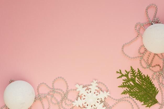 휴일 크리스마스 배경, 전나무 가지 및 은색 장식 구슬, 흰색 눈송이 및 분홍색 배경의 크리스마스 공, 평평한 평지, 위쪽 전망
