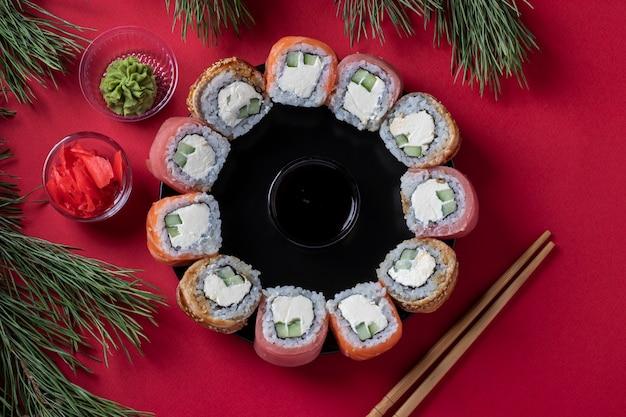 Праздничный рождественский бранч суши набор из лосося, тунца и угря с сыром филадельфия в виде венка на красном фоне. вид сверху