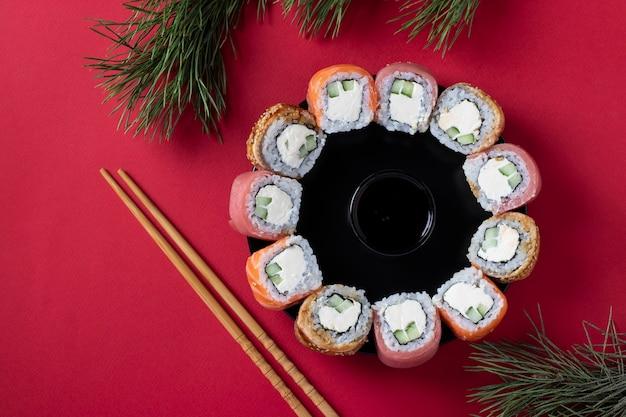 Праздничный рождественский бранч суши из лосося, тунца и угря с сыром филадельфия в виде венка на красном фоне. вид сверху
