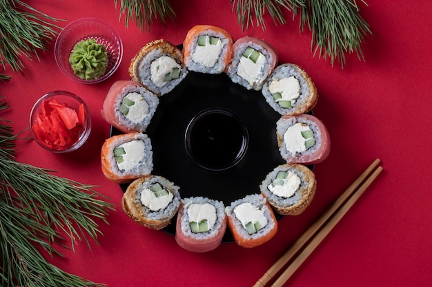 Holiday christmas brunch sushi set of salmon, tuna and eel with philadelphia cheese as a wreath on a red background. top view
