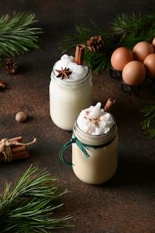 茶色の背景にシナモンとナツメグとメイソンジャーの休日のクリスマスエッグノッグ飲料